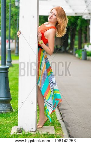 Beautiful Girl Peeping From Behind Pillar Gazebo In The Park