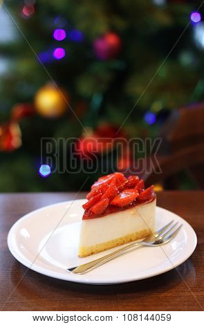 Fresh strawberry cheesecake. Selective Focus on the front upper edge of cake. Christmas tree in back