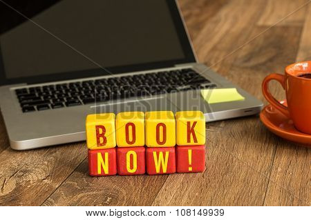 Book Now! written on a wooden cube in front of a laptop