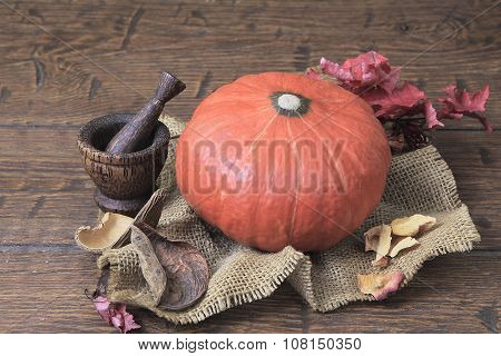 Orange Pumpkin And Vintage Mortar With Pestle On  Homespun Canvas