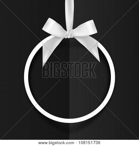 White holiday round frame with bow and silky ribbon on black background