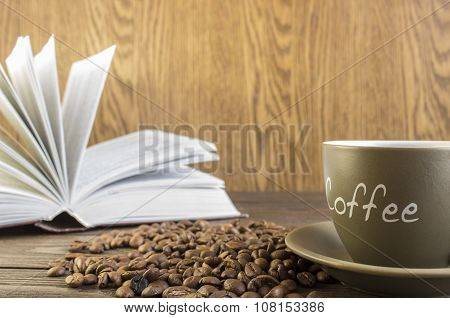 Cup of coffee with beans in front of open book standing on a wooden table. Crop blurred focus on mug