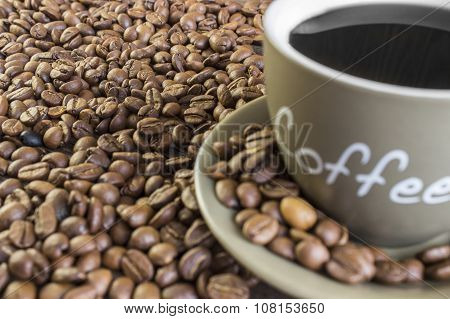 Cup of coffee with beans standing on a wooden table. Crop blurred focus on farthest beans