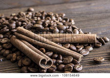 Coffee beans and cinnamon sticks bark lie on a wooden table. Blur focus on near-stick