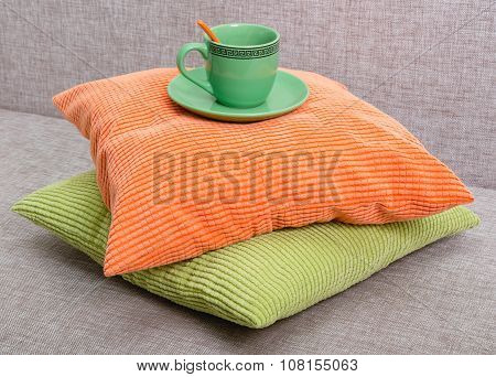Ceramic Green Cup With A Saucer And An Orange Teaspoon On A Pile From Green And Orange Pillows On A