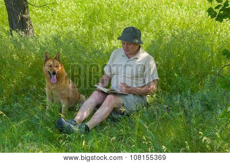 Mature man reading an interesting book to young dog