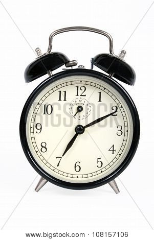 Classic old black alarm clock on white background