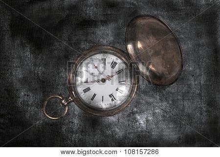 Antique pocket watch on a dark vintage background.