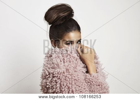 Smiling Woman Closed Her Face With A Faux Fur Jacket And Watchig