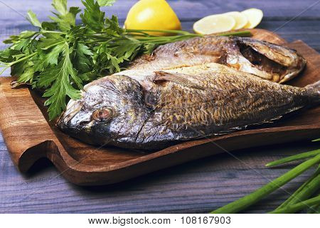 On A Wooden Table Plate With Two Roasted Carp Fish Dorado