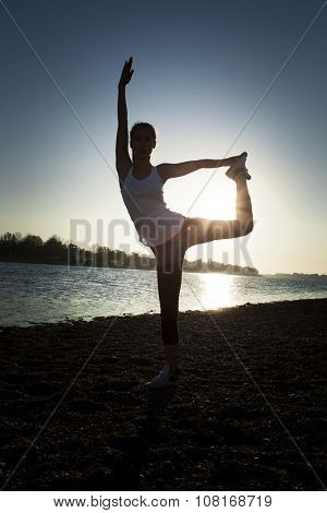 girl exercise balance by the lake  autumn day, full body shot, silhouette