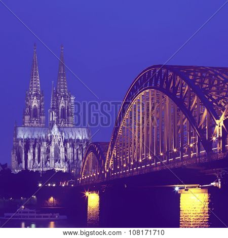 Cologne cathedral and railway bridge at night.