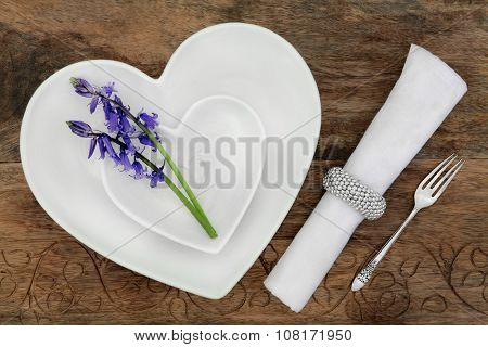 Elegant place setting with white heart shaped porcelain bowls, bluebell flowers, napkin and antique silver fork over old oak table background.