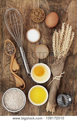 Baking ingredients and kitchen equipment with rye grain in lovespoon and wheat sheath bundle over old wood background.