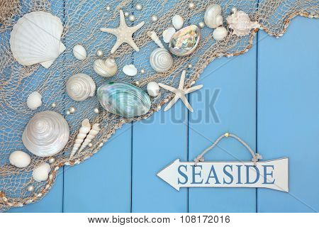 Abstract scene with seaside sign, shells, pearls and fishing net over wooden blue background.
