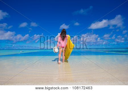 Young happy woman relaxing with air mattress during tropical vacation
