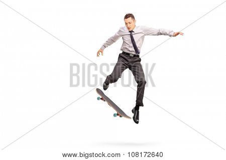 Studio shot of a young businessman performing a trick with a skateboard shot in mid-air isolated on white background