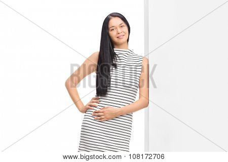 Studio shot of a woman posing in a white dress with black stipes and leaning on a wall isolated on white background