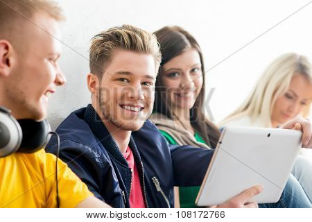 Group of students on a break. Focus on a happy boy using tablet. Background is blurry.