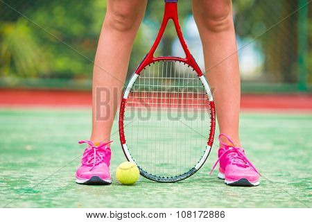 Closeup of shoes with the tennis racquet and ball outdoors on court