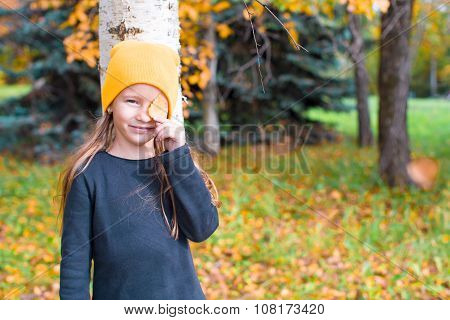 Little girl playing hide and seek near tree in autumn park