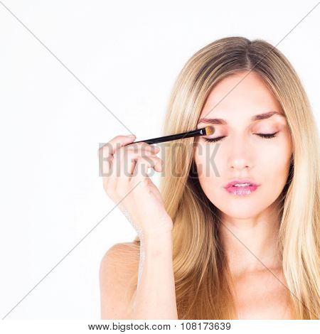 Beautiful woman paints eyelid with a cosmetic brush. Make up.