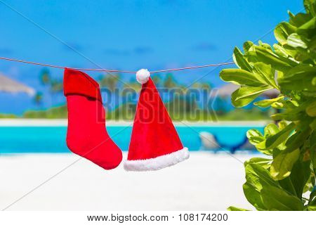 Red Santa hat and Christmas stocking between palm trees on white beach