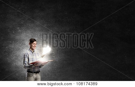 Young man holding opened book and glass glowing bulb on pages