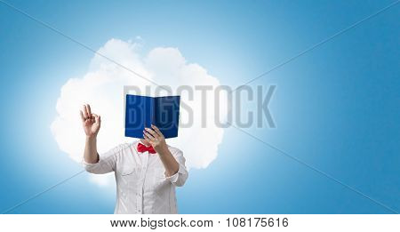 Senior woman with opened book against her face showing ok gesture