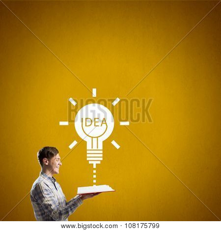 Young man with opened book on color background