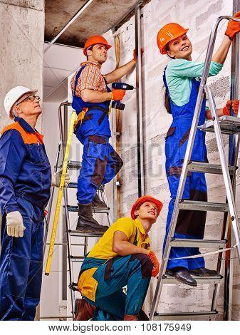 Happy group people in builder uniform indoor on stair.