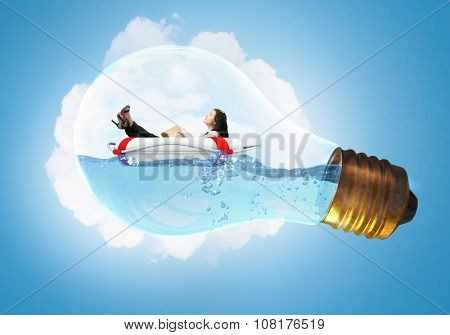 Young businesswoman floating on life buoy inside of light bulb