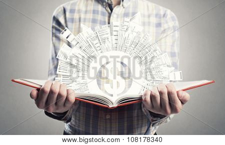 Young man in casual holding opened book with dollar sign