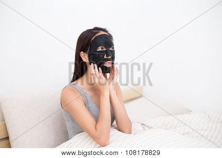 Woman using the black sheet paper mask