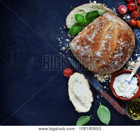 Homemade bread loaf and fresh ingredients for making sandwiches (tomatoes, basil, olive oil, cream cheese) on rustic dark background. Cooking, Healthy or vegetarian eating concept.