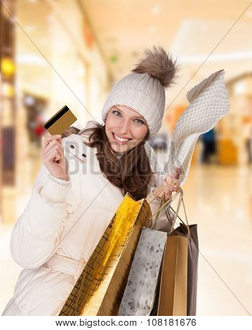 Happy brunette girl in winter dress posing in shopping mall, holding credit card