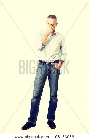 Mature man holding his nose because of sinus pain.
