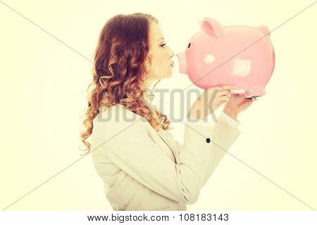 Happy business woman kissing a piggybank.