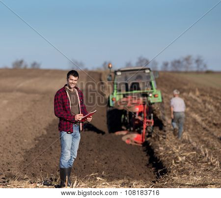 Farmer With Tractor On Field