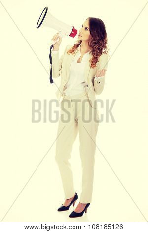 Beautiful businesswoman shouting with megaphone.