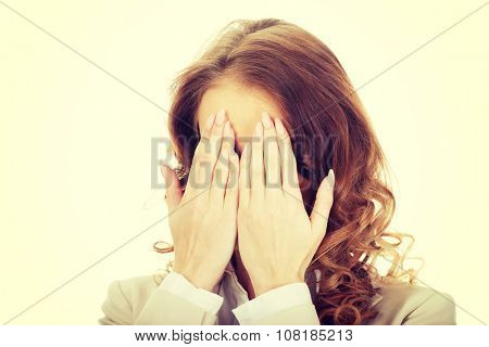 Young businessman covering face by hand.
