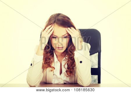 Beautiful worried businesswoman at the desk.