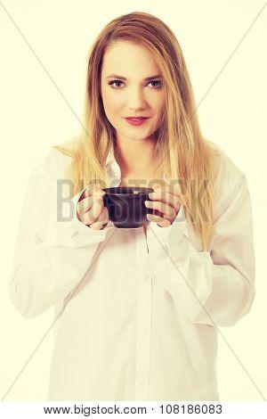 Beautiful woman in long sleeve shirt drinking coffee.