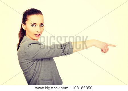 Beautiful confident businesswoman pointing aside.