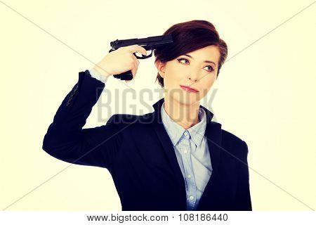Despair businesswoman holding a gun near head.