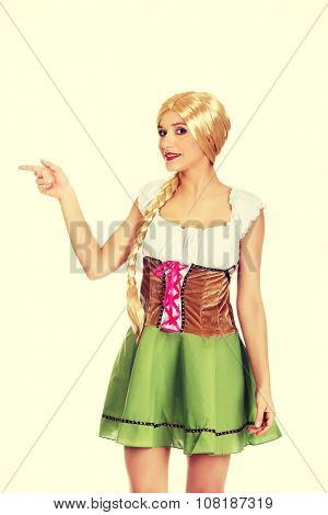 Woman wearing traditional Bavarian dress pointing aside.