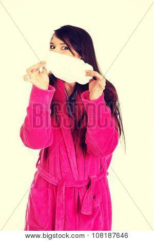 Caucasian woman in pink bathrobe with menstruation pad.