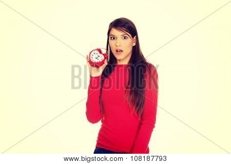 Shocked student woman with alarm clock.