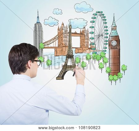 A Handsome Young Man Is Drawing A Colourful Sketches Of The Most Popular Cities In The World. The Co