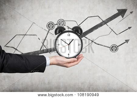 A Businessman's Hand Holds An Alarm Clock. There Is A Growing Line Charts Behind The Alarm Clock. A